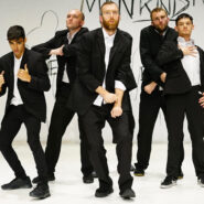 group of 5 male dancers in suits on a white stage
