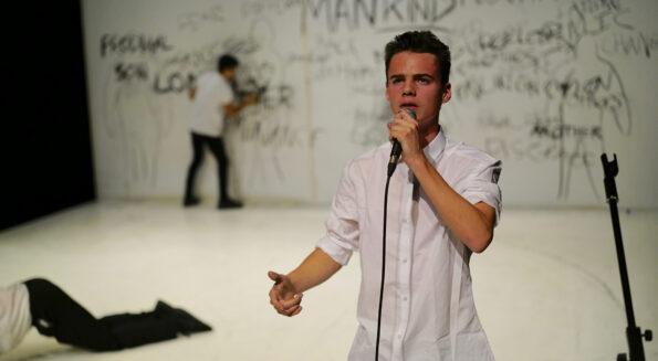 Brighton spoken word artist Eben'Flo at a mic on a white stage