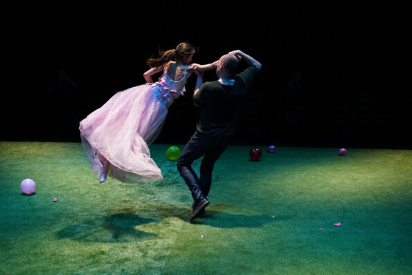 A man dances with a young teenage girl in a pink ball gown
